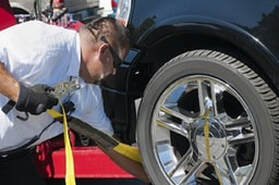 a man fixing the car's position on the tow truck