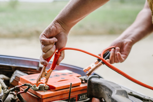 putting a jumper cables on a car battery